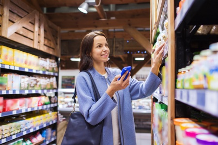 Amazon goes grocery shopping: Woman shopping in store using mobile phone