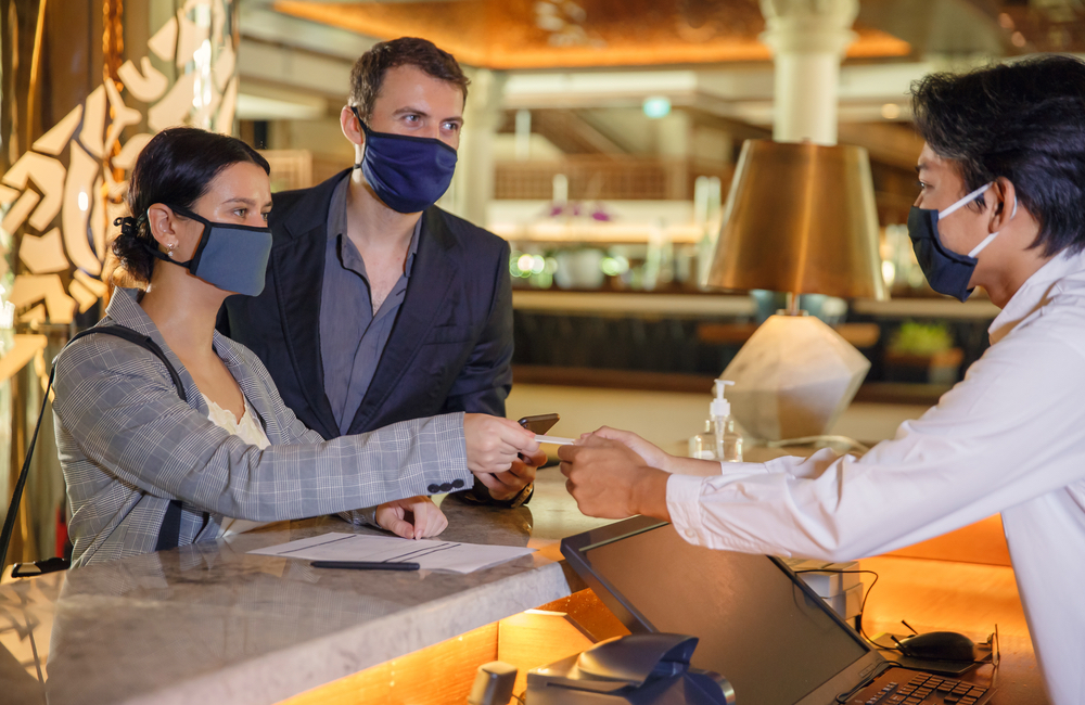 Answer Guest Questions With Digital Tools: Guests Checking Into Hotel Wearing Masks