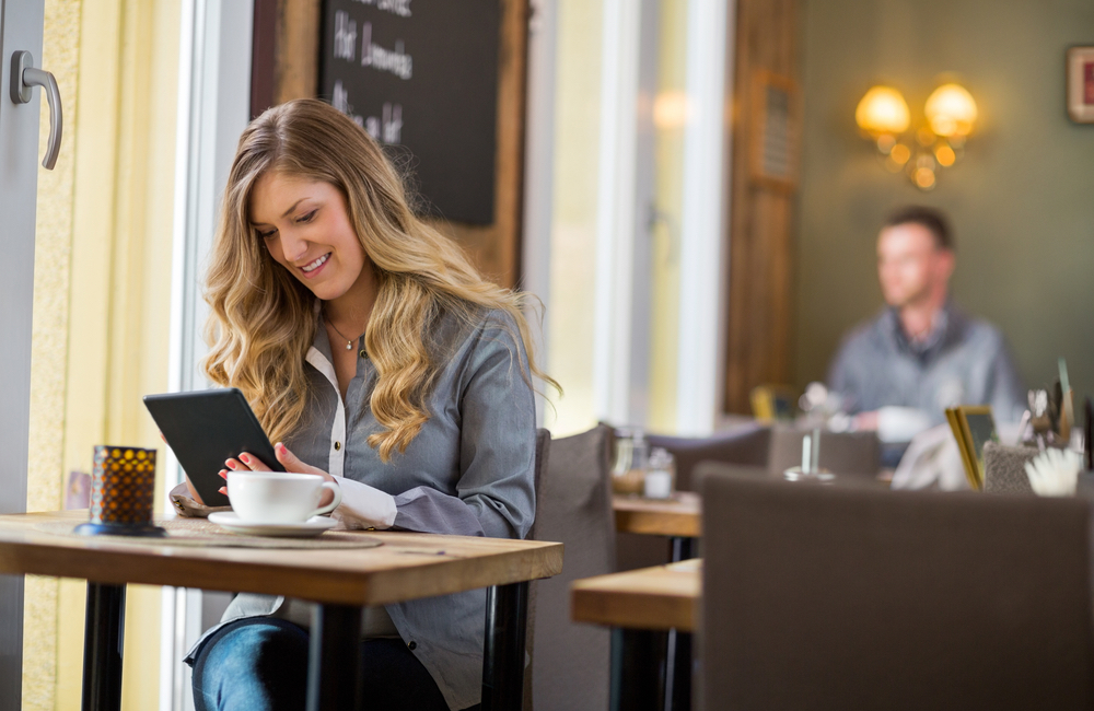 Digital Transformation Is About Customers: Young Woman Using Tablet At Restaurant Table
